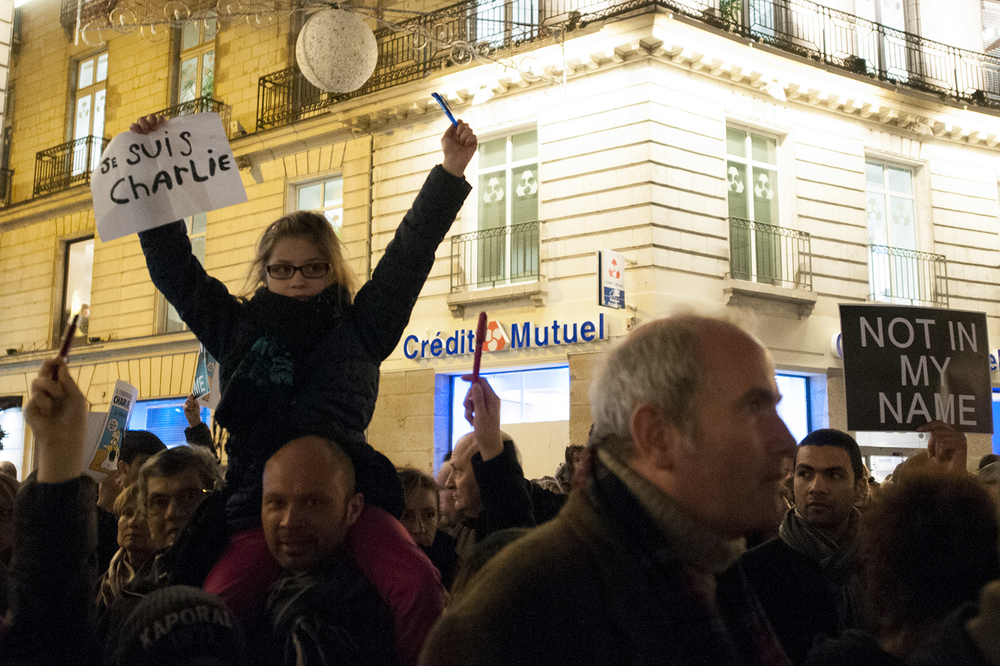 "little girl holding up a pen and a sign saying ""I am Charlie"""
