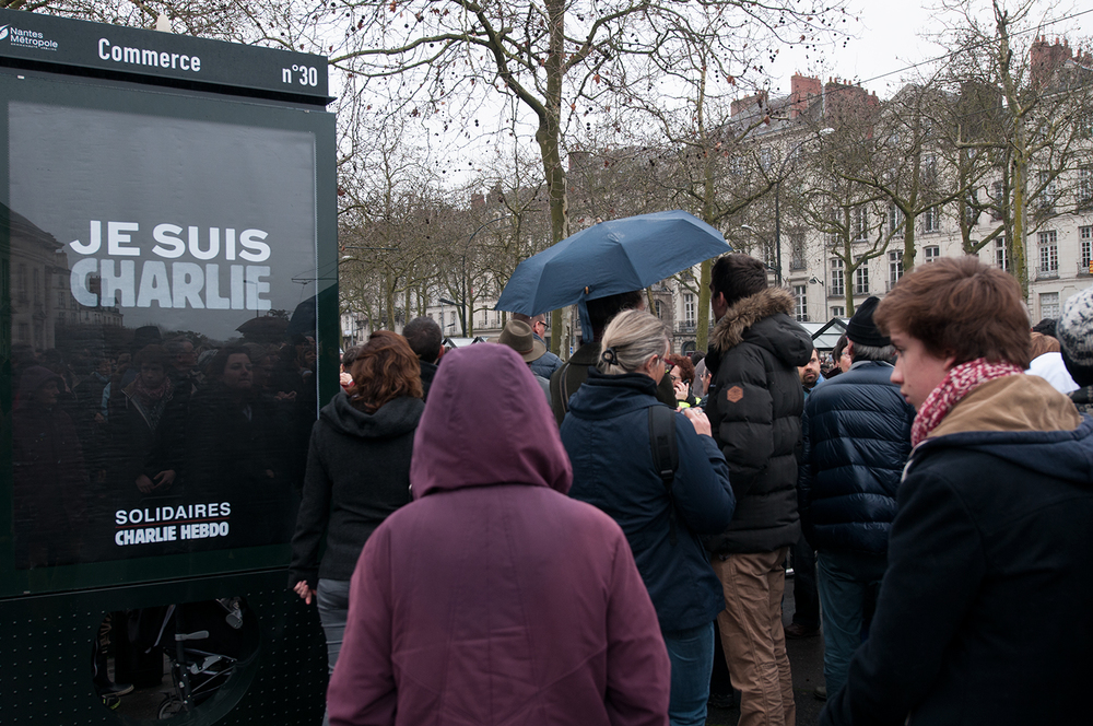 "People passing by a poster ""I am Charlie, Supporting Charlie Hebdo"""