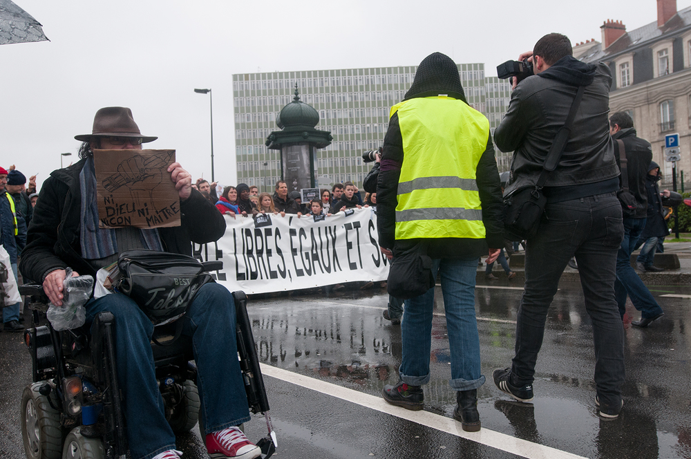 "A man in a wheelchair holding a sign saying ""Nor god, nor master, nor moron"""