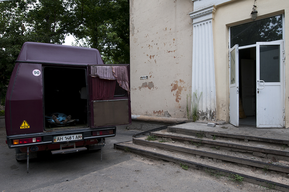 A vehicle parked in front of the morgue's door with the corps of a man inside of it