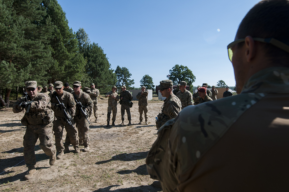 U.S. paratroopers demonstrating how to clear a room to Ukrainian soldiers.