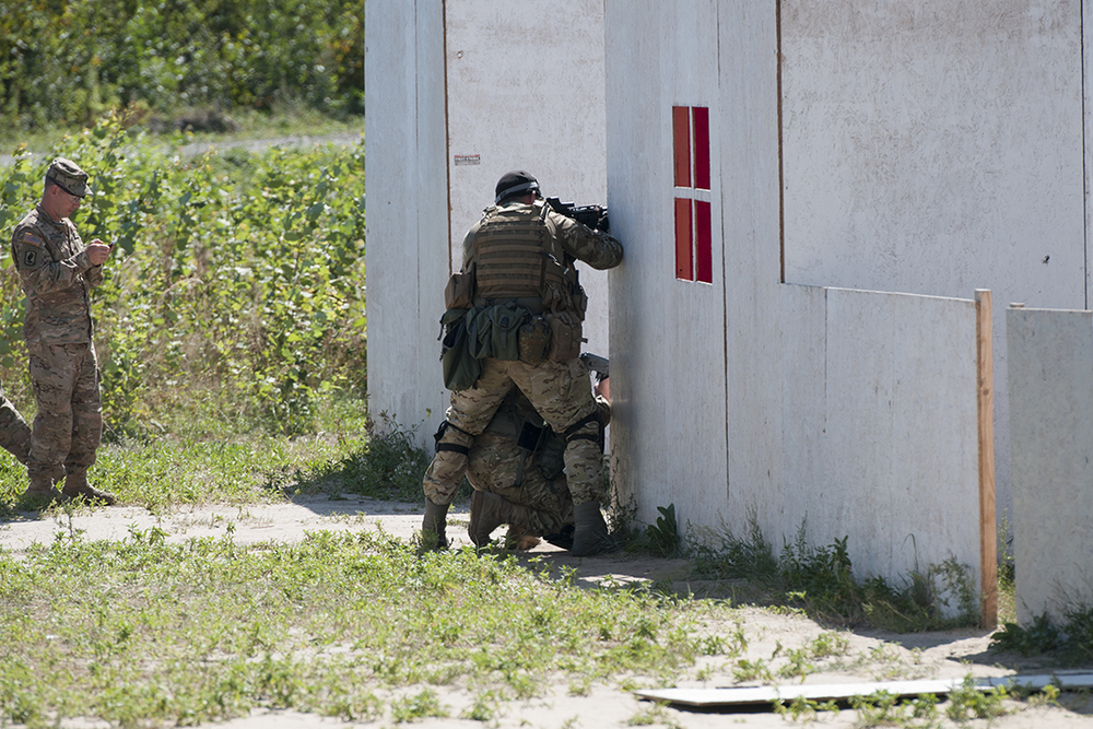Ukrainian soldiers peaking at the corner of a fake building while an American officer monitor the exercise.