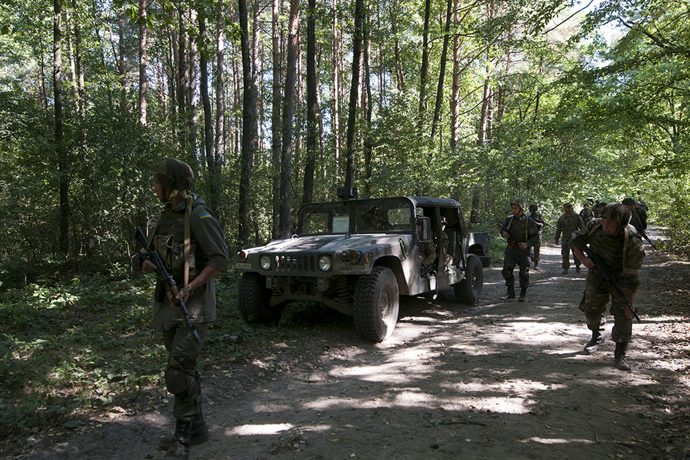 Ukrainian soldiers walking past an American HUMVEE during a patrol exercise.