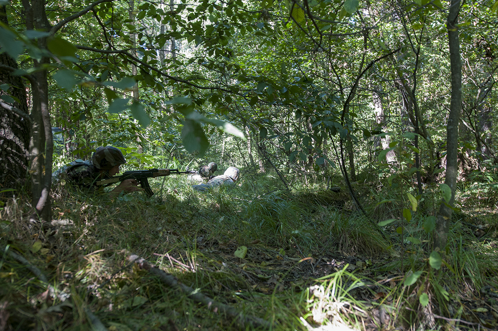Ukrainian soldiers hitting the ground and returning fire after being ambushed by U.S. soldier during the patrol exercise.