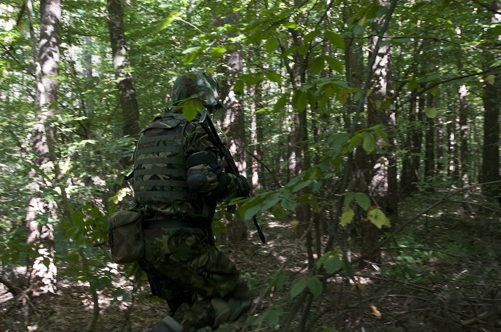 Ukrainian soldier from the national guard running through the forest towards the attackers position during a patrol exercise.
