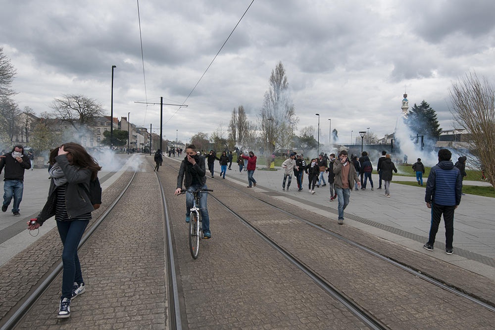 A cyclist protecting himself and ridding away from tear gas.
