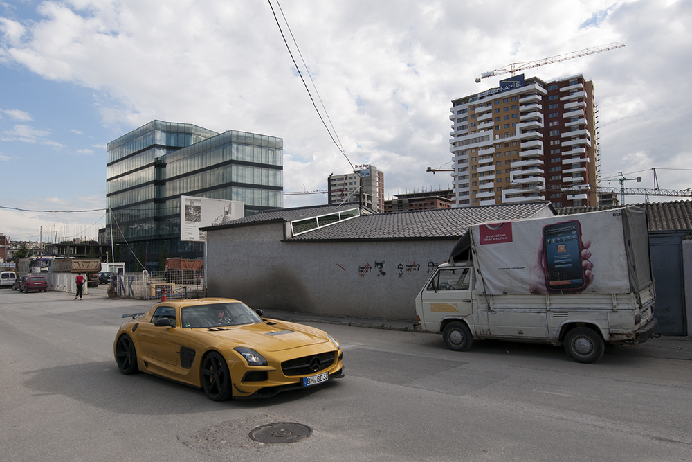 Mercedes AMG with a German number plate driving through a neighborhood under construction.