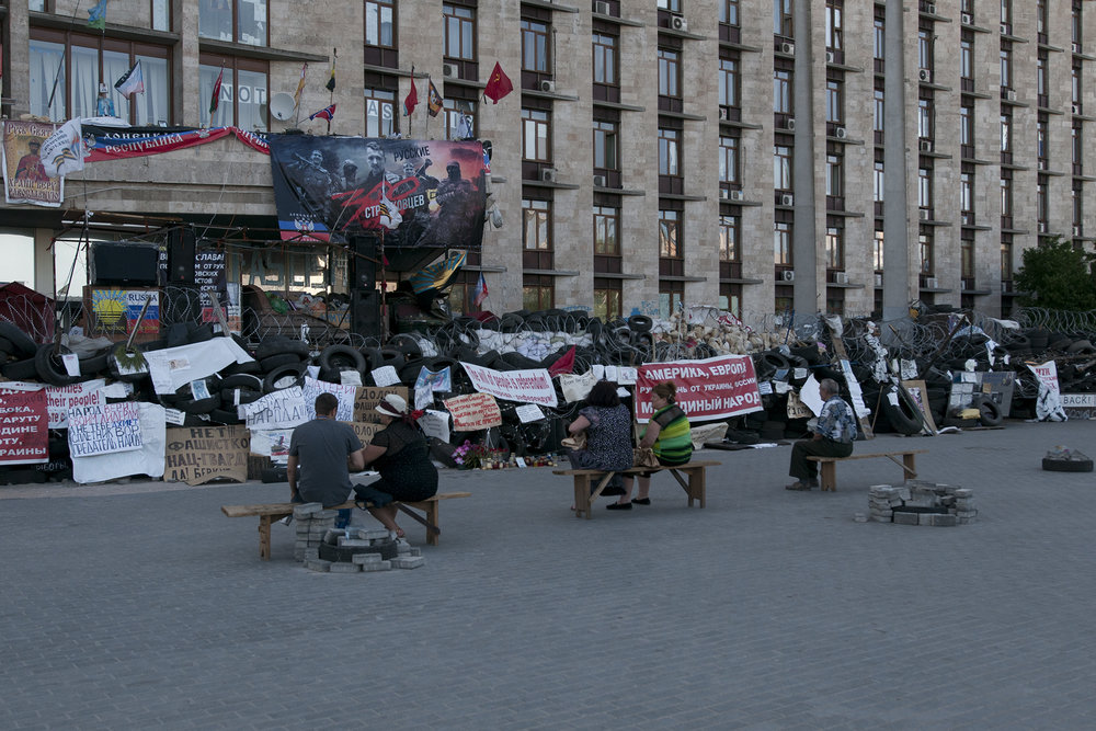 People sitting in front of Donetsk Regional Building