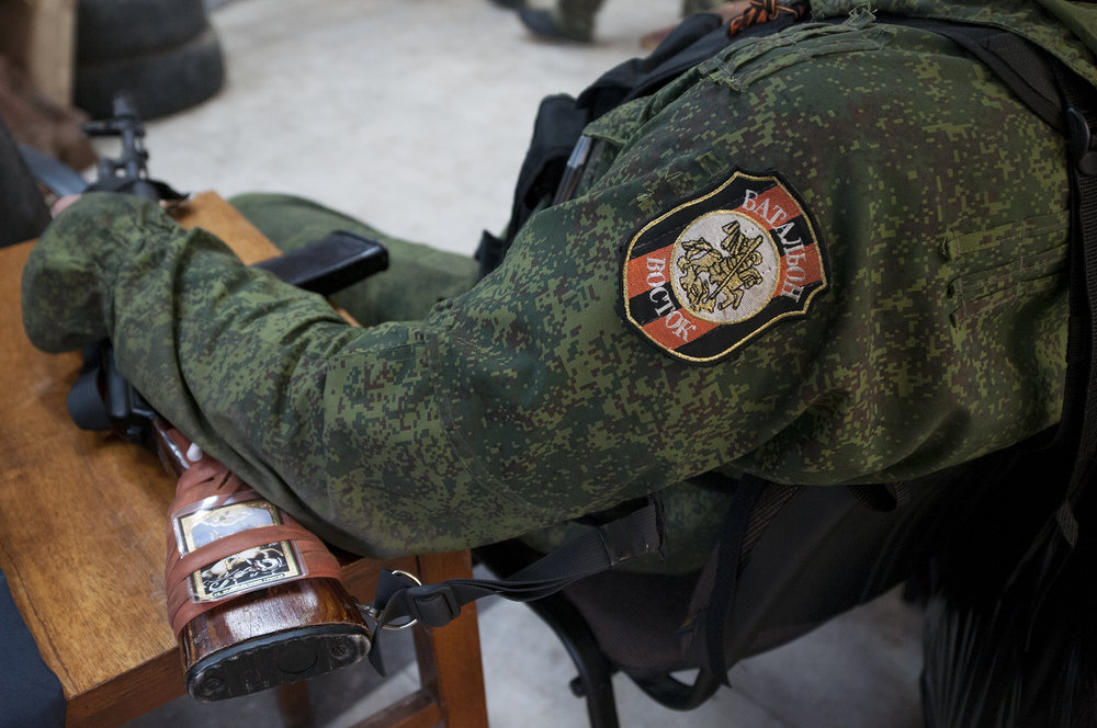 Vostok Battalion soldier resting on a chair with his gun tucked underneath his forearm