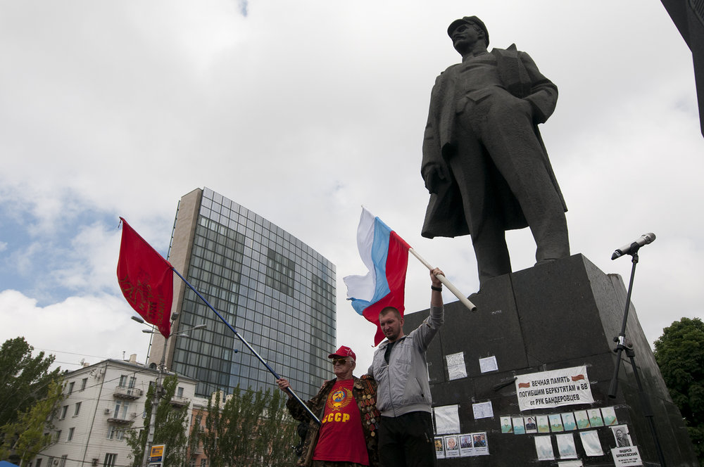 Two men holding a Russian flag and an other one from the USSR underneath a statue of Lenin