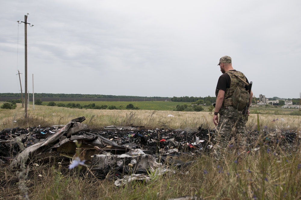 Pro-Russian soldiers looking over the remains of MH17 passengers scattered accross debris of the plane