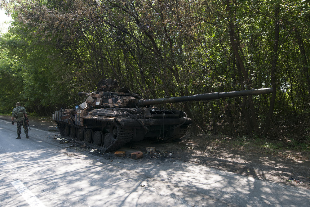 Separatist soldier looking at destroy Ukrainian tank from Azov Battalion