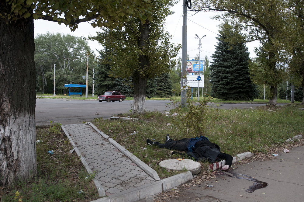 Remains of a man laying on the sidewalk after he has been killed by shrapnel