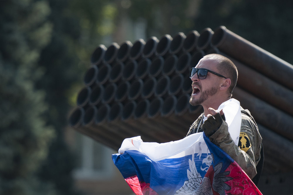A pro-Russian rebel holds a Russian national flag near a damaged GRAD luncher from the Ukrainian army during an exhibition in the central square of Donetsk