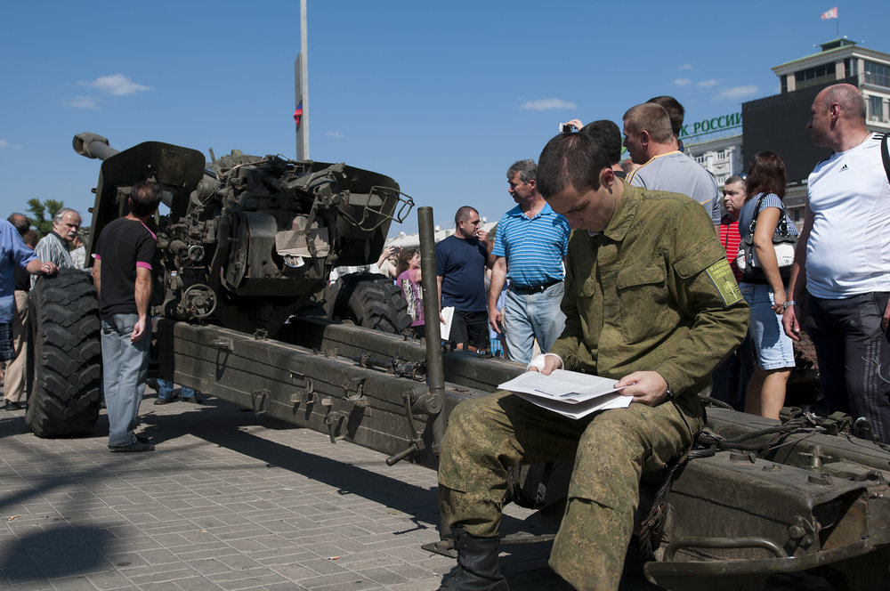 Pro-Russian rebel reading a propaganda newspaper while sitting on a howitzer piece captured from the Ukrainian Forces put on display for inhabitants of Donetsk to see