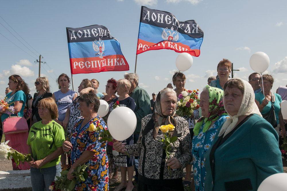 Local residents holding flowers and flags of the self-proclaimed Donetsk People's Republic attend the one year memorial ceremony at the crash site of the Malaysian Airlines MH17
