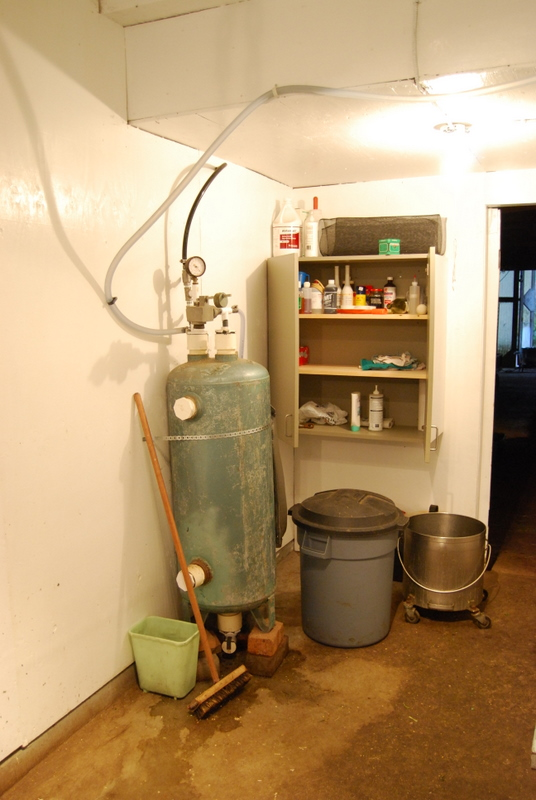 Supplies cupboard and compressed air tank for auto milker