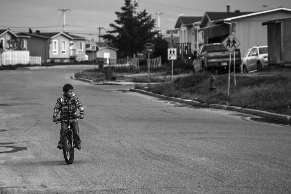 Un jeune se balade en vélo sur la rue Poplar