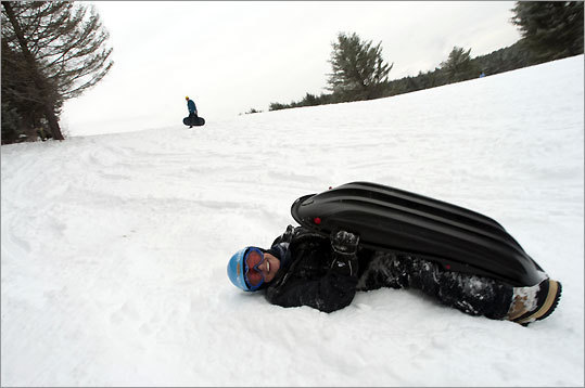 Mary Anne Machis of Stowe is headed the wrong way at Marshall Hill, called the ''town sledding hill.'' (Caleb Kenna for The Boston Globe)