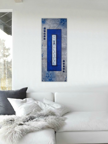 asian style abstract painting in cobalt blue hanging on white living room wall