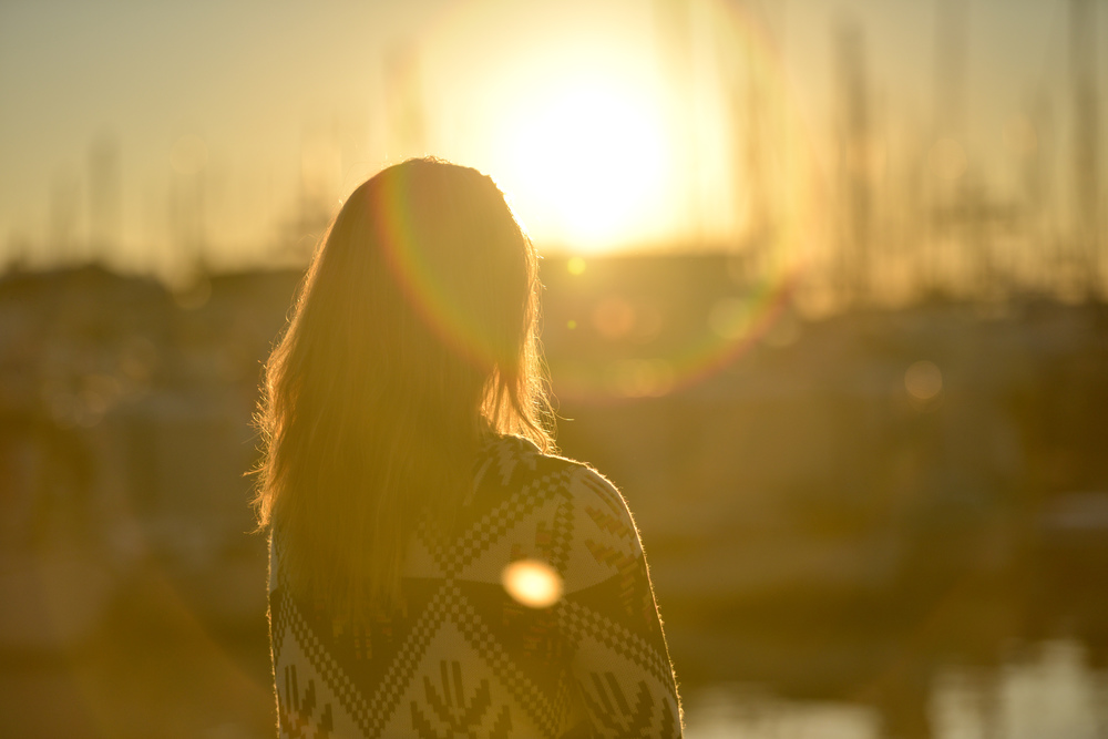 Image is of a woman staring at the sun rising or setting on the horizon.