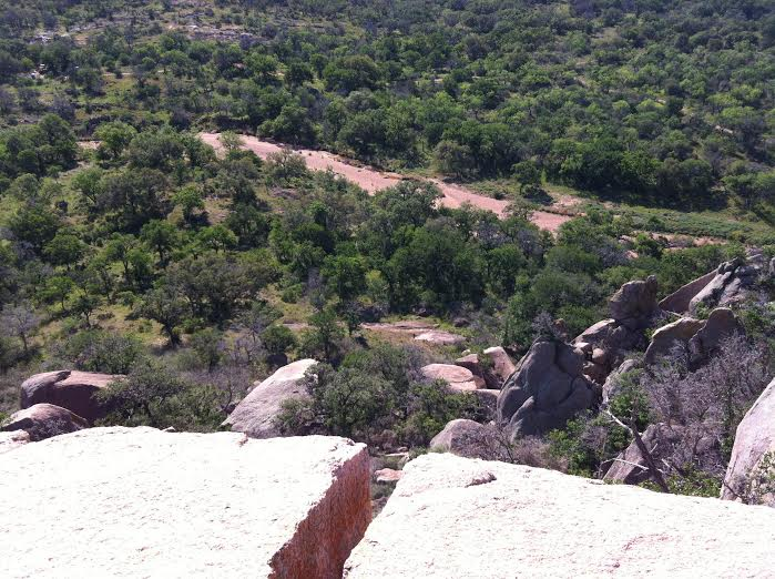 This photo is a crack in the rock face in Enchanted Rock State Park near San Antonio. After making several attempts to climb up the rock face using the crack, my friends and I walked around the rock formation to look down at it from above. The change in perspective was strange. Everything looked different from up above.  by Caitlin Eley