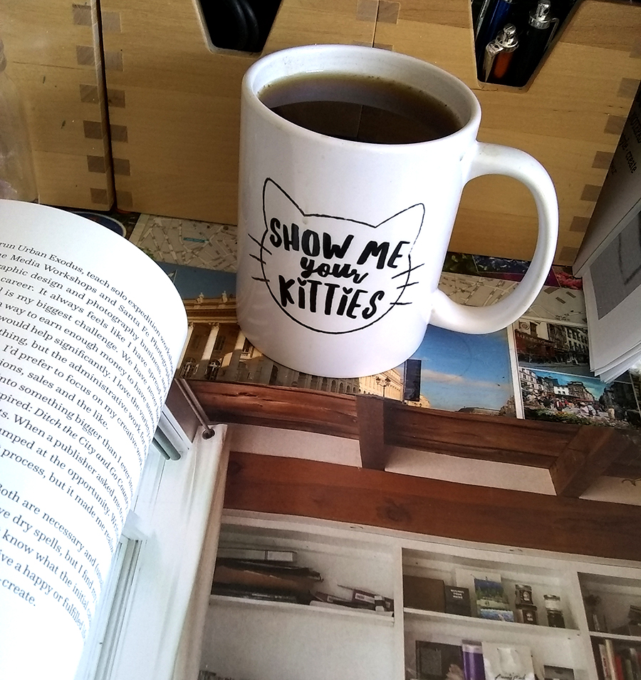 (Before I got the new desk.) Reading a magazine about women artists and their art studio spaces. I've gotten a couple of these magazines, and they're a great source of inspiration for my art studio space, and motivating me in my art practice. Also, coffee.