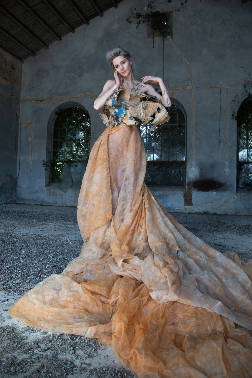 Roxanna Walitzki, shot by Redd Walitzki, in an abandoned paint factory in Pula, in a dress constructed from naturally-weathered cardboard packaging paper, and pigment-stained mesh sourced on site.