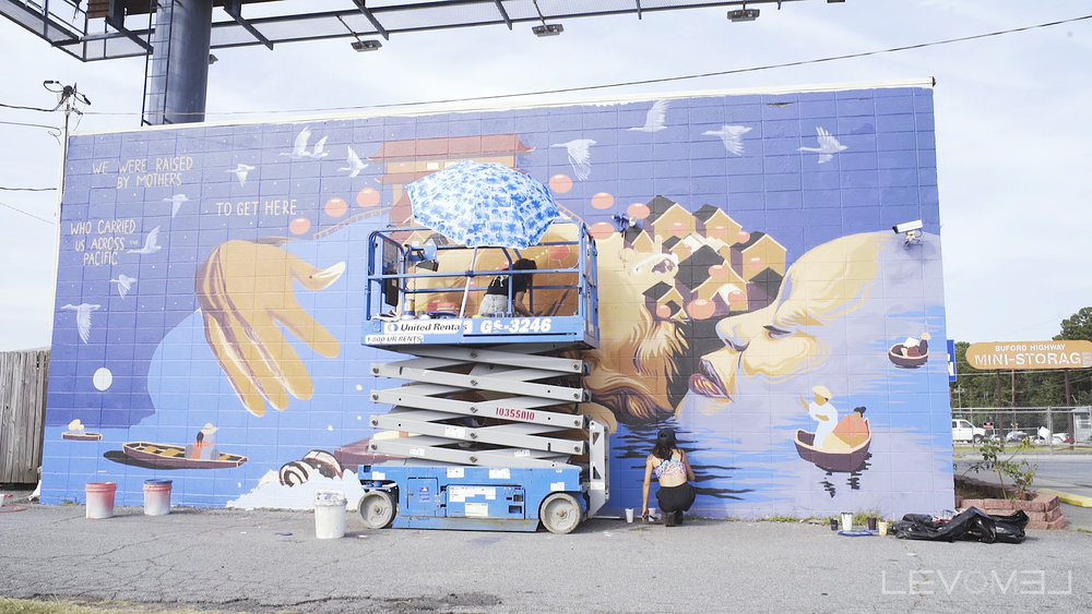 Jess Snow  putting up one of TWO beautiful murals on Bufford Highway last week.