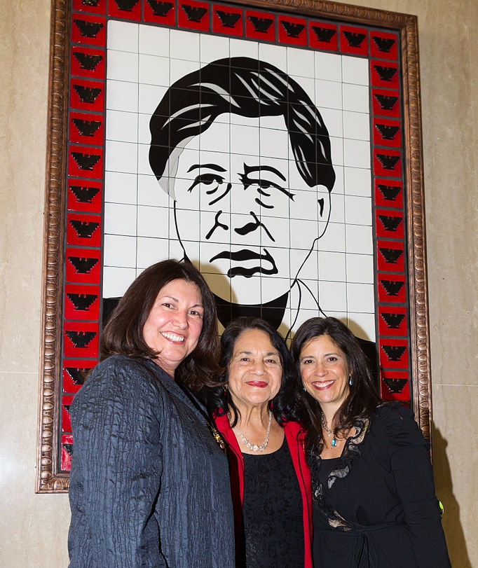 Dolores Huerta under an illustration of Chávez at the César Chávez Memorial Auditorium. Photo by the US Department of Labor.