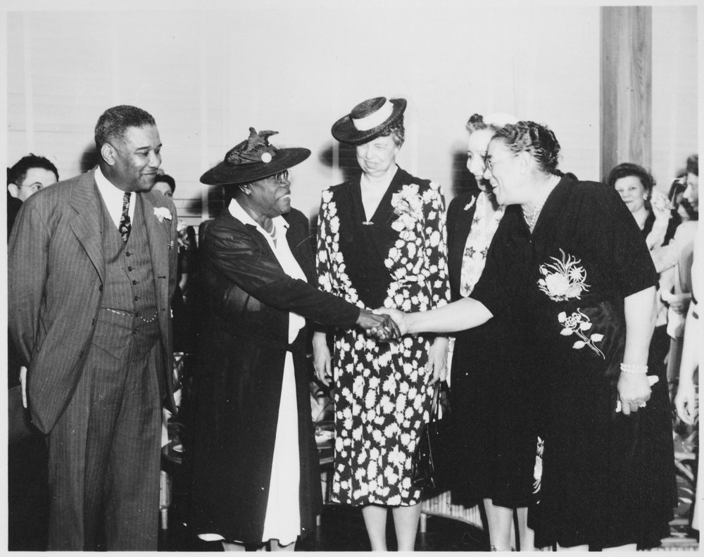 Mary McLeod Bethune, Mrs. Eleanor Roosevelt and others at the opening of Midway Hall, one of two residence halls built by the Public Buildings Administration of FWA for Negro government girls. From the General Records of the Federal Works Agency. National Archives Identifier: 533032