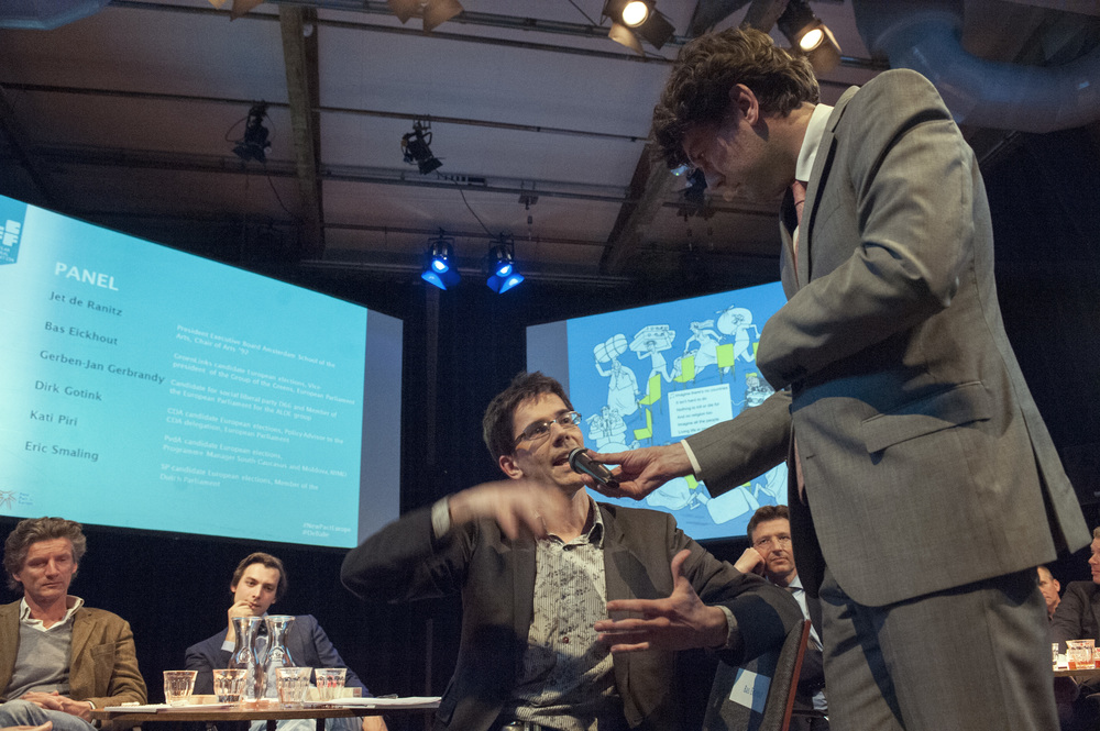 Moderator Lennart Booij and Bas Eickhout, with a  cartoon by Payam Boromand  in the background ©Jan Boeve
