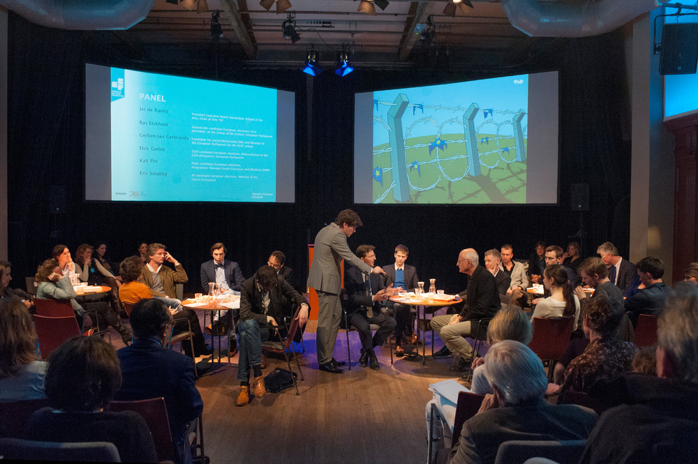 The debate panelists with  the cartoon  European Border  by Tjeerd Royaards  shown in the background ©Jan Boeve