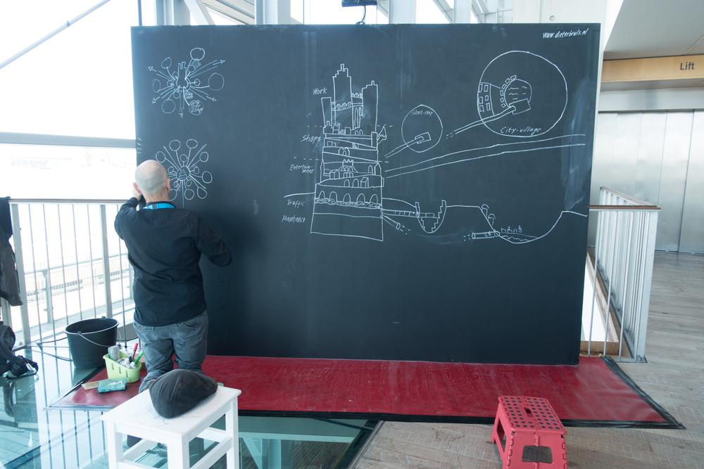 Artist Dieter Bruls working on his utopic city during Urbo Kune at    the Muziekgebouw aan 't IJ.Photo by Canan Marasligil
