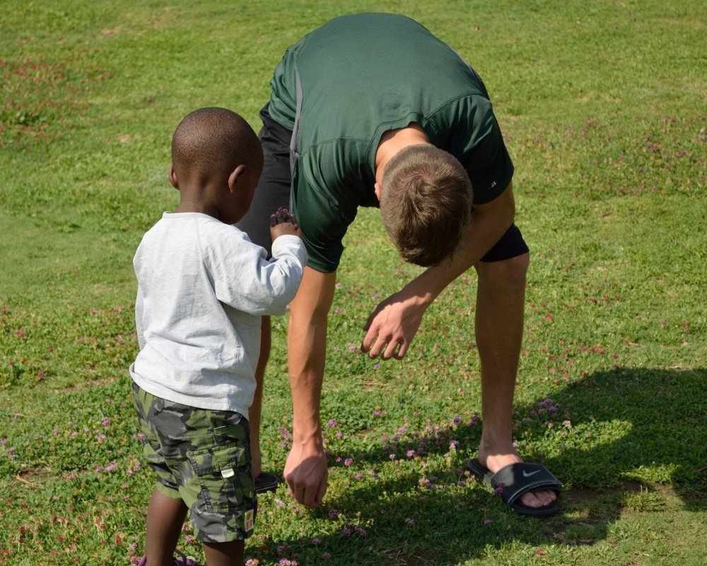 Kam getting down to the kids' level to play (and enjoy the allure of the clover, a favorite of the children).
