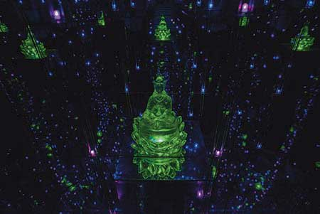 Photo from the Fa-Tsang Mirror House at Tsogyelgar. The alchemical chamber draws the MindHeart into natural contemplation. An octagonal room, mirrored on all sides, with a single Buddha statue and LED lights creates infinite Buddhas and infinite lights expanding though infinite space — all within a small room.
