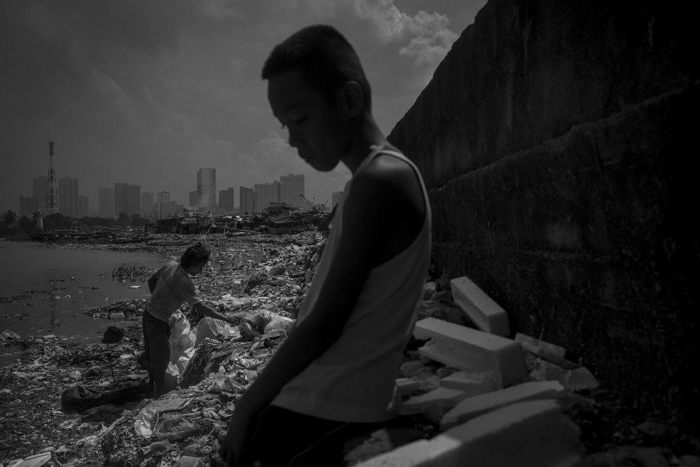 Arjay Onbrog looks to domestic waste in Pasig River as Hilario Bomong tries to collect recyclables.