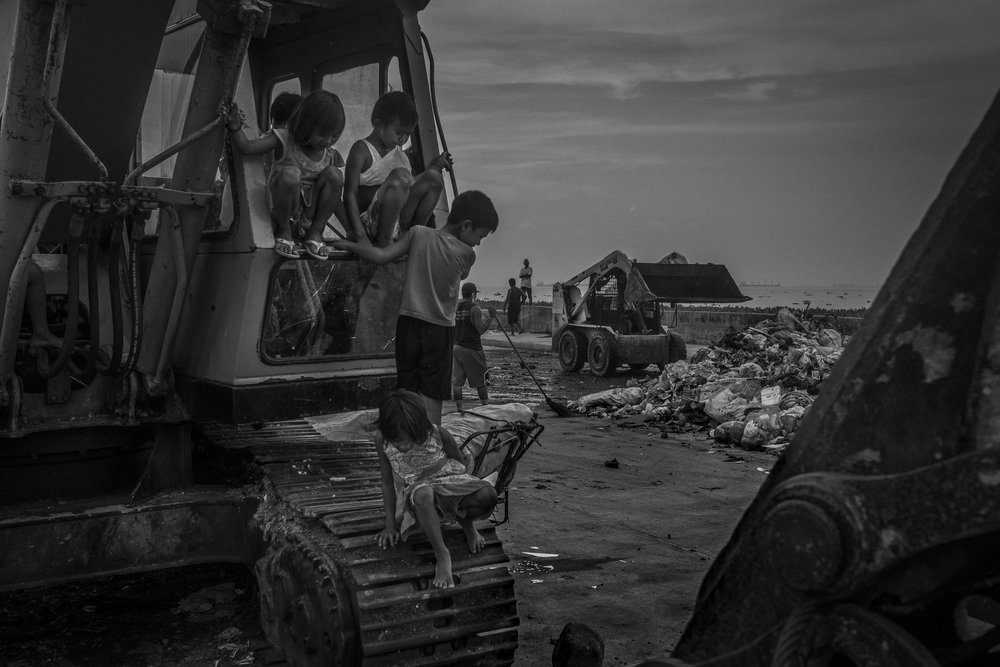 Children play on a excavator as others collect a pile of garbage along the banks of the Pasig River.