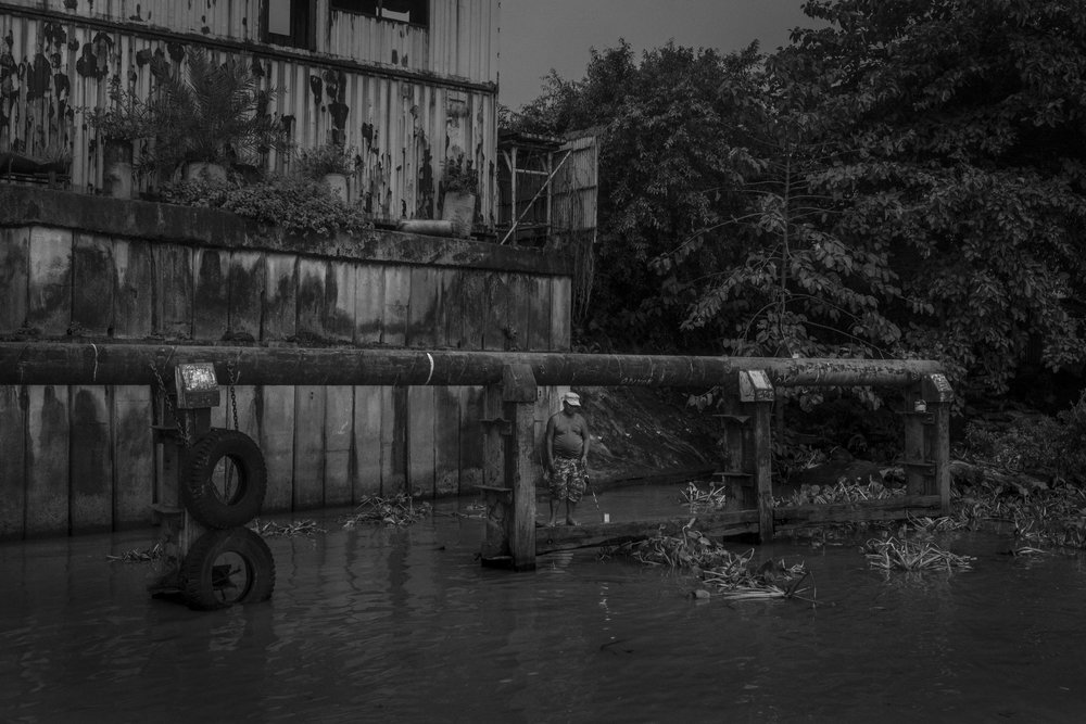A man fishing next to a disabled industrial building on the banks of Pasig River.