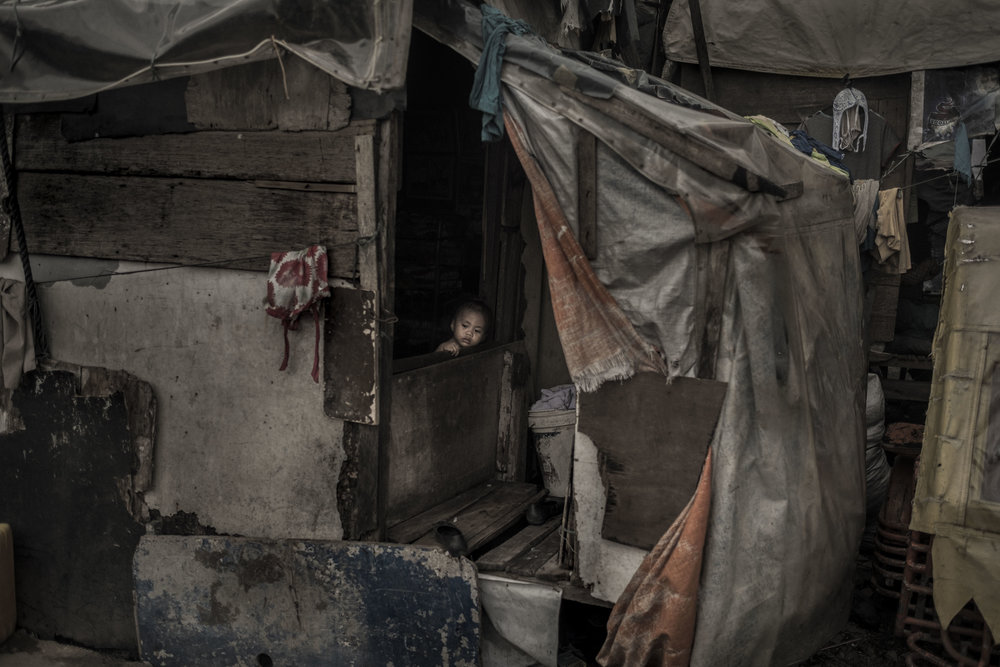 A child looks outside from a house made of materials found in the Pasig River.