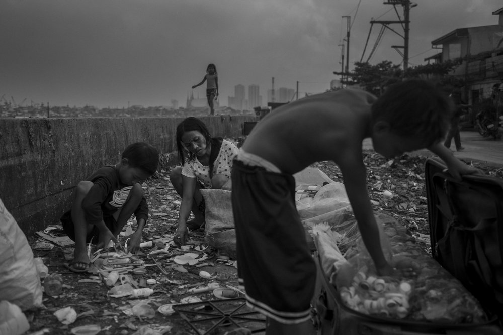 Jocelyn Balbin and her sons Mark and Reynaldo collect water caps and other recyclable materials, next to Pasig River, in Manila, Philippines.