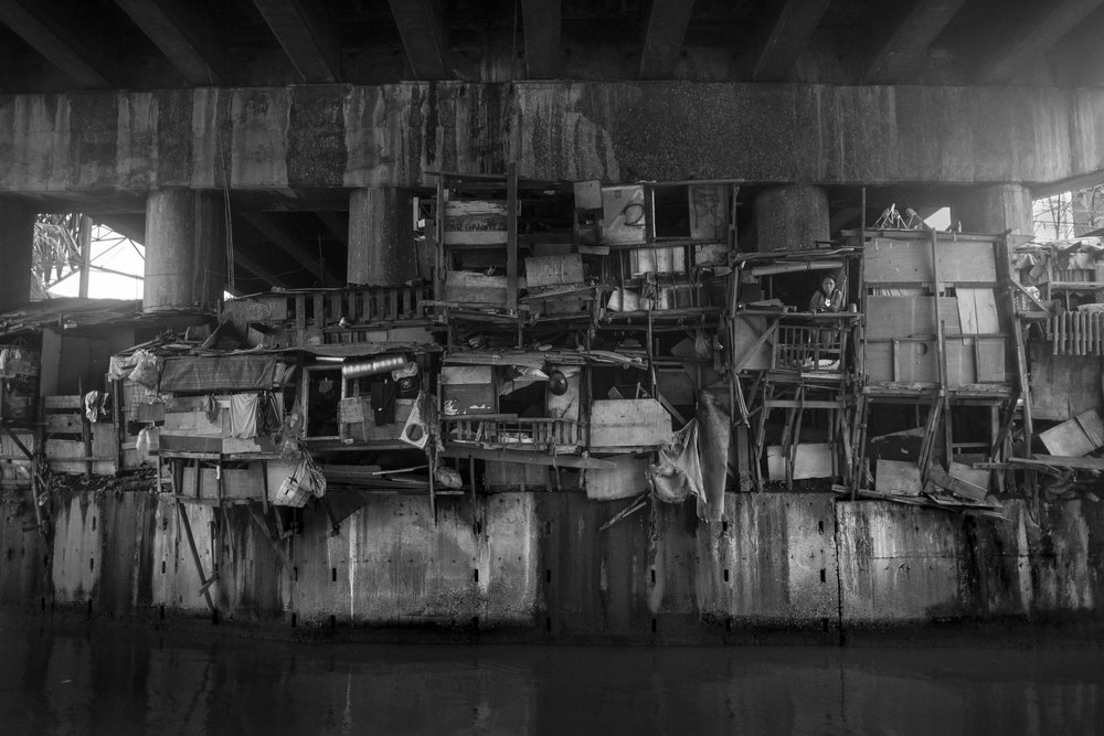 Houses built under a bridge crossing the Pasig River in Manila.