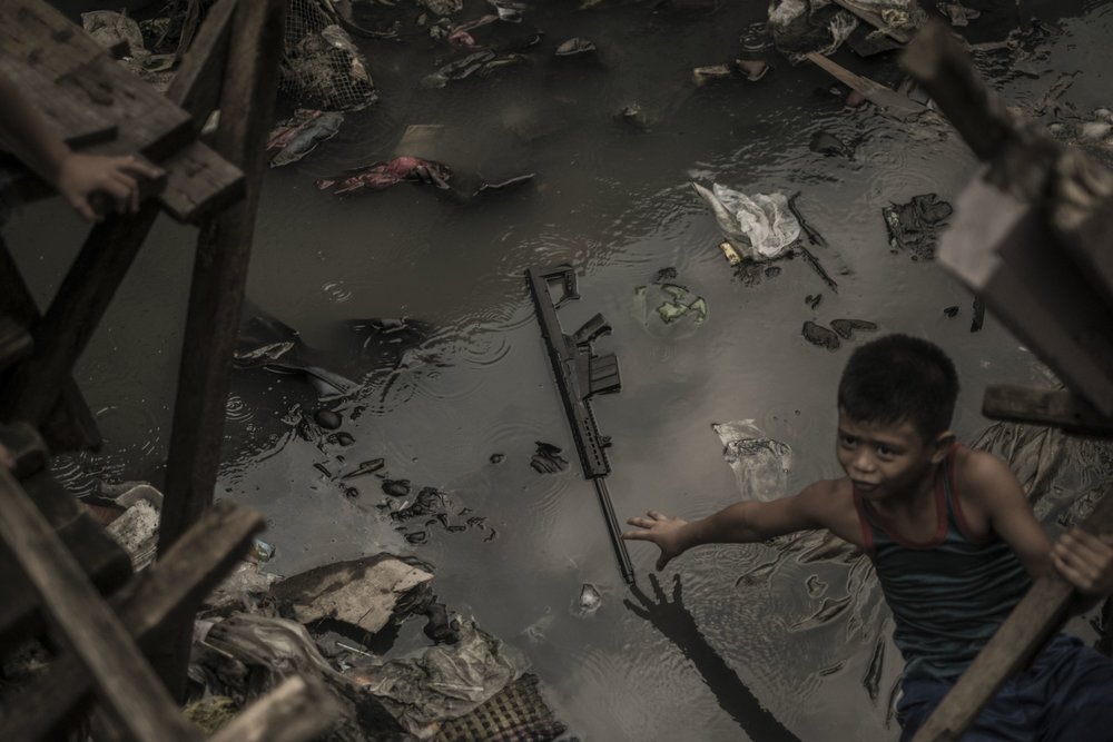 A boy tries to pick up a toy gun floating on the polluted waters of Estero de Magdalena.