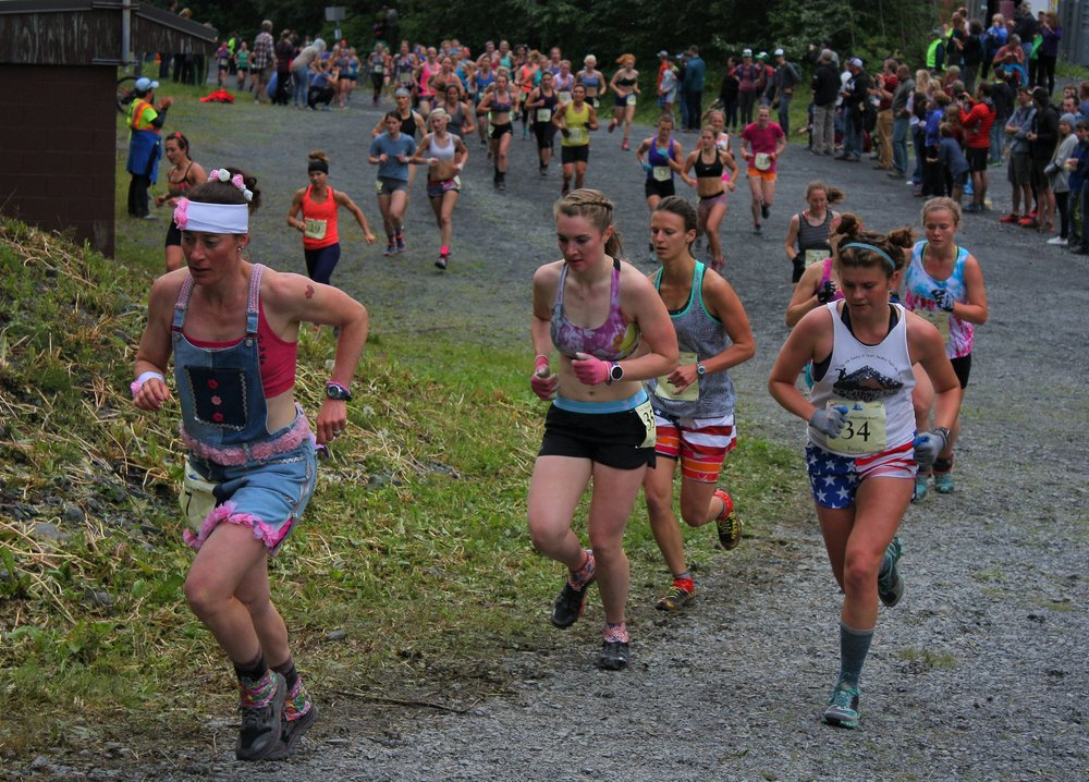 Aubrey Smith, left, known for her denim get-ups, leads a pack of ladies up Mount Marathon for the annual Fourth-of-July race this year.