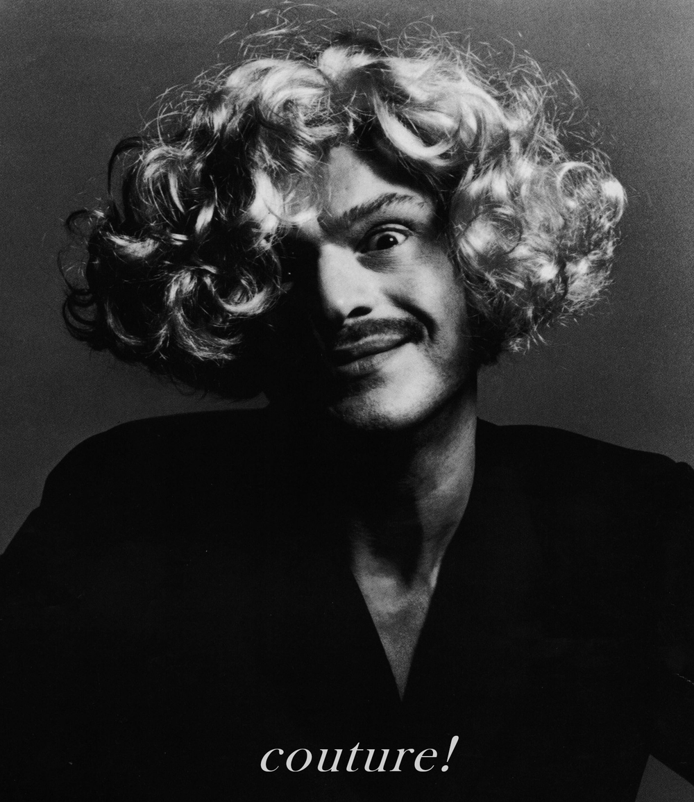 """Franco Moschino (1950-1994), pictured here with a wig in place of his famous crew cutfor one of his advertisements, which famously questioned the fashion industry with cries of, """"Stop the Fashion System!"""",""""This is not an advertisement! Couture!"""" or """"Warning: Advertising Can Cause Serious Damage to Your Brain and to Your Wallet!"""""""