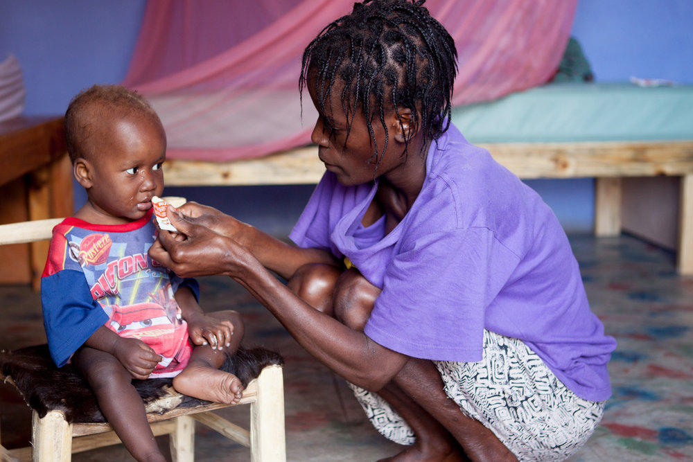 "A mom in the program at  Second Mile  feeds her nephew ""plumpy nut,"" a fortified peanut butter paste packed with all the vitamins he needs to recover from acute malnutrition and get healthy."