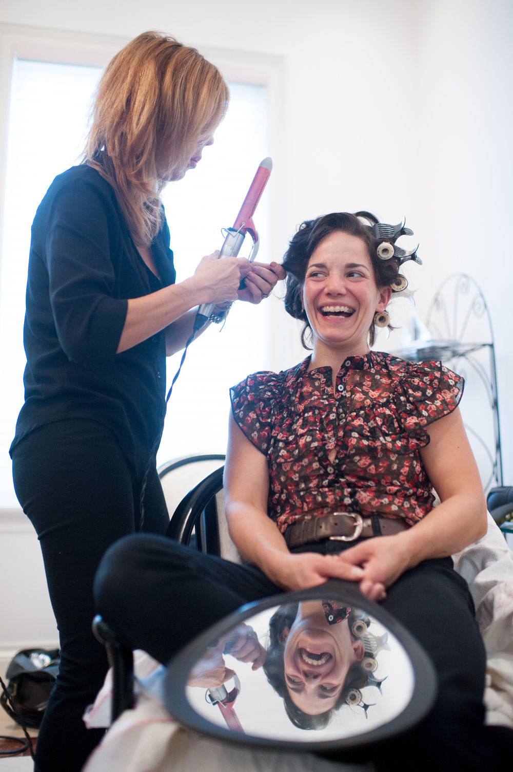 bridesmaid laughs while having her hair done at brides home.