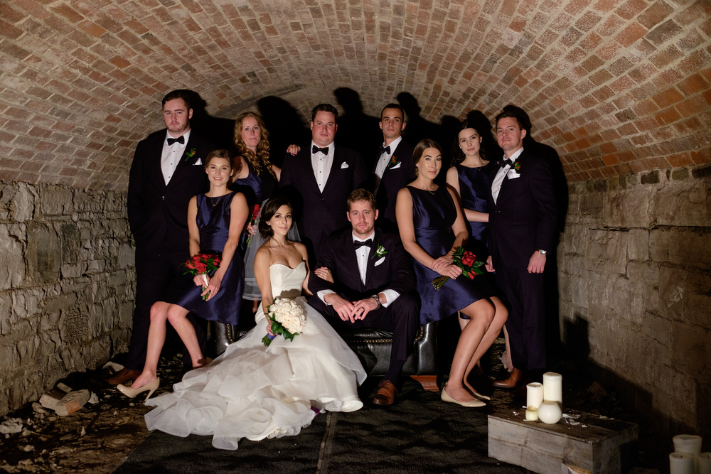 Spencer and Jonas pose with their wedding party for a cool portrait in the old bootlegger tunnels under the Stirling Room.
