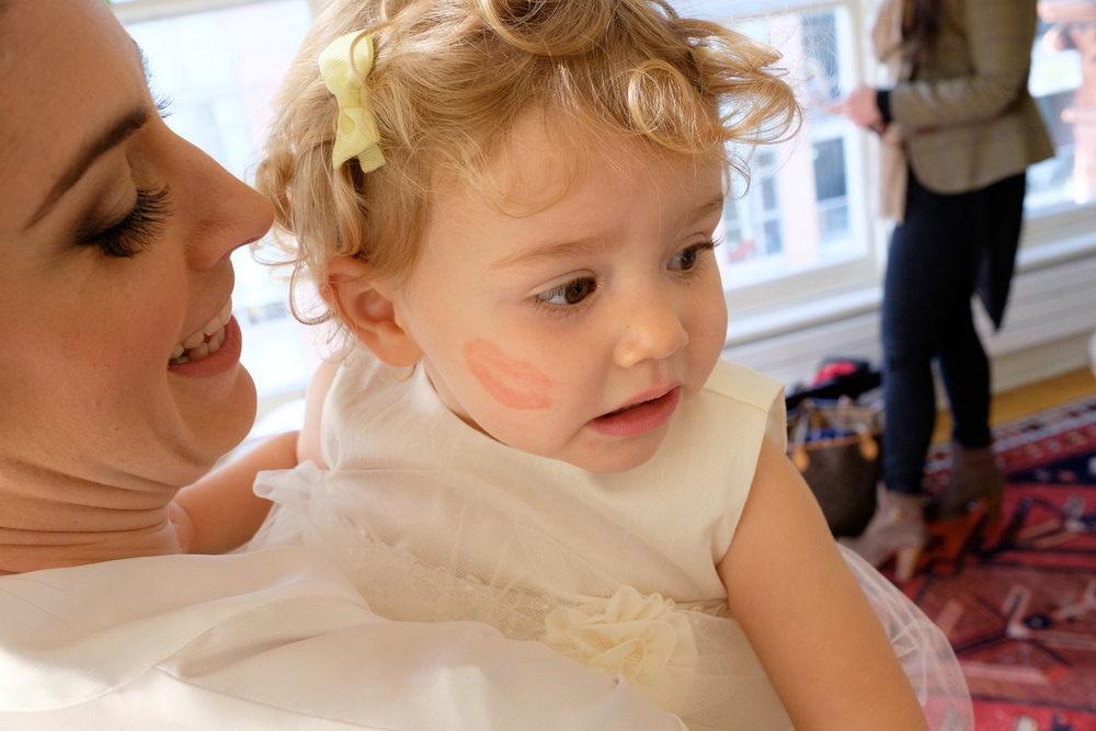 The bride leaves a lipstick kiss on the cheek of her adorable flower girl while getting ready at the Gladstone Hotel.
