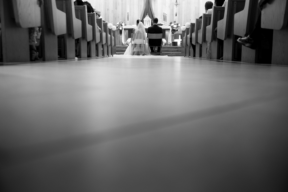 A photograph of Olivia + David during their wedding ceremony from the back of the church.